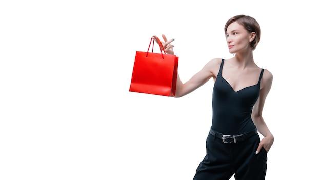 Portrait de femme adulte élégante qui pose en studio sur fond blanc avec sac cadeau rouge. concept de la saint-valentin. vacances et cadeaux. technique mixte