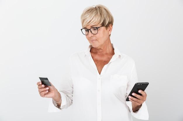 Portrait d'une femme adulte joyeuse aux cheveux blonds courts tenant un téléphone portable et une carte de crédit isolée sur un mur blanc en studio