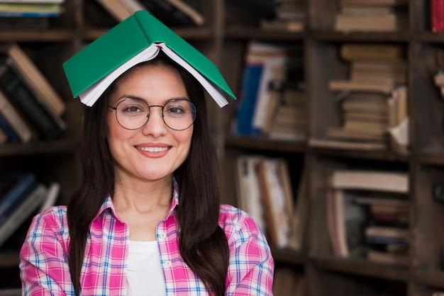 Portrait de femme adulte posant avec livre