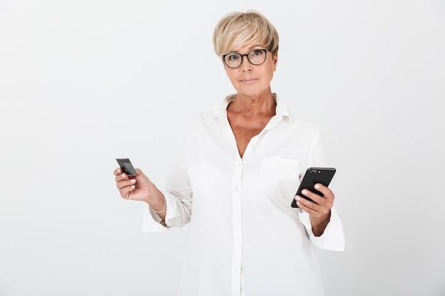 Portrait d'une femme adulte de race blanche aux cheveux blonds courts tenant un téléphone portable et une carte de crédit isolée sur un mur blanc en studio