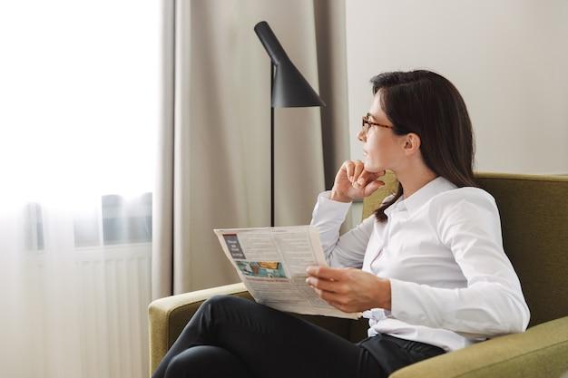 Portrait d'une femme d'affaires adulte brune en costume formel lisant le journal assis dans un fauteuil près de la fenêtre à l'intérieur