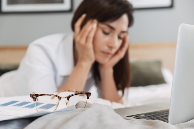 Portrait d'une femme d'affaires adulte épuisée en costume formel travaillant avec un ordinateur portable et des documents papier en position couchée sur le lit dans l'appartement
