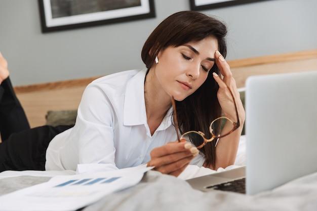 Portrait d'une femme d'affaires adulte fatiguée en costume formel travaillant avec un ordinateur portable et des documents papier en position couchée sur le lit dans l'appartement