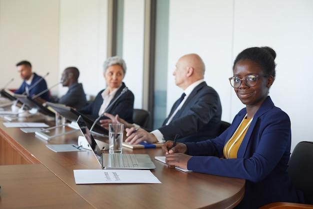 Portrait de femme d'affaires africaine à la recherche alors qu'il était assis avec ses collègues lors d'une conférence d'affaires