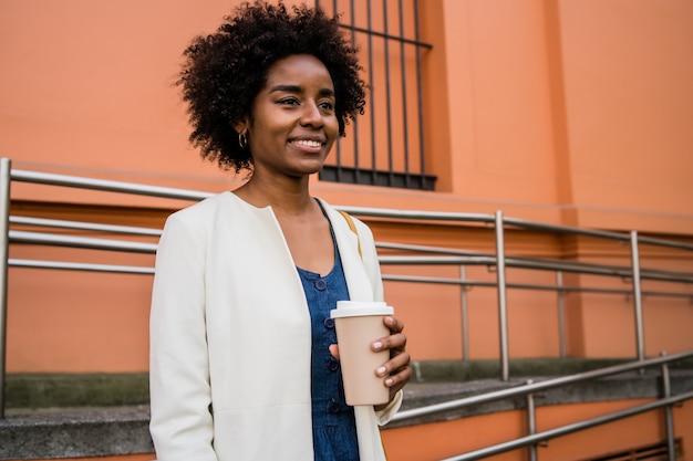 Portrait de femme d'affaires afro tenant une tasse de café en se tenant debout à l'extérieur dans la rue. concept d'entreprise et urbain.