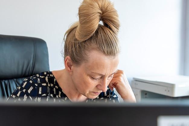 Portrait de femme d'affaires d'âge moyen au travail derrière l'écran d'ordinateur, instantané inattendu
