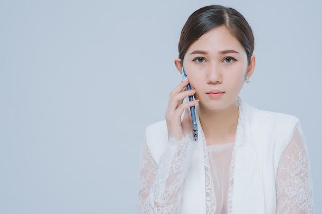 Portrait de femme d'affaires asiatique sur appel téléphonique sur fond gris