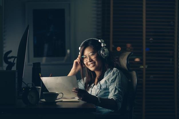 Portrait de femme d'affaires asiatique assise et travaillant dur avec bonheur
