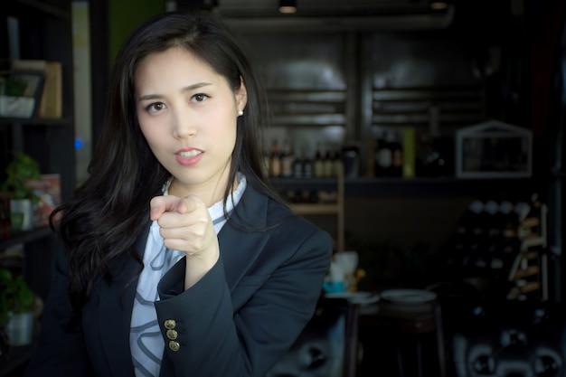 Portrait de femme d'affaires asiatique attrayant en costume pointant son doigt vers vous