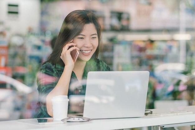 Portrait de femme d'affaires asiatique en costume décontracté parler et travailler avec la technologie portable à happine
