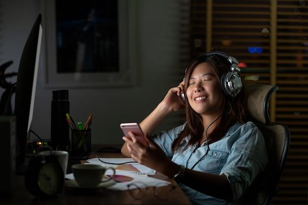 Portrait de femme d'affaires asiatique écoutant de la musique via un casque et un téléphone mobile intelligent