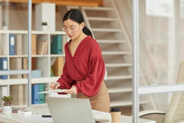 Portrait de femme d'affaires asiatique moderne debout au bureau dans un bureau moderne, femme patron ou secrétaire, espace copie
