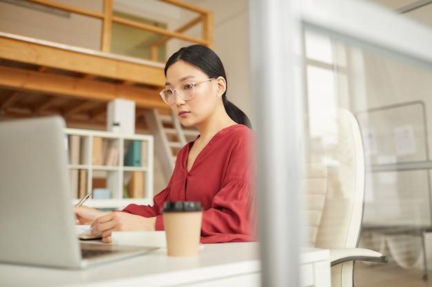 Portrait de femme d'affaires asiatique réussie à l'aide d'un ordinateur portable tout en travaillant au bureau dans un bureau blanc moderne, concept de femme patron, espace copie