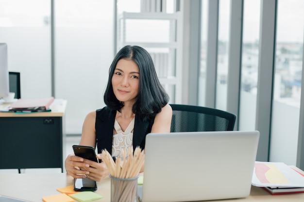 Portrait de femme d'affaires asiatique réussie à l'aide de téléphone et travaillant au bureau moderne