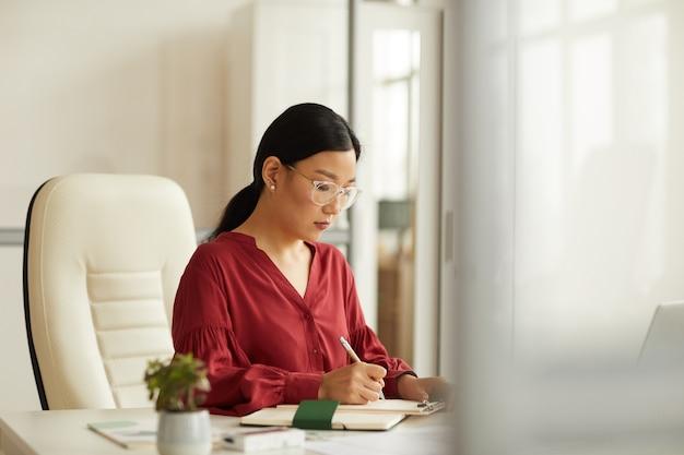 Portrait de femme d'affaires asiatique réussie portant chemisier rouge travaillant au bureau dans un bureau blanc moderne, espace copie