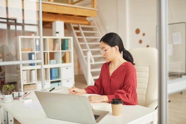 Portrait de femme d'affaires asiatique réussie travaillant au bureau dans un bureau blanc moderne, concept de femme patron, espace copie