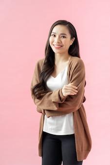 Portrait d'une femme d'affaires asiatique souriante debout avec les bras croisés et regardant la caméra isolée sur fond rose
