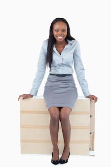 Portrait d'une femme d'affaires assis sur un panneau