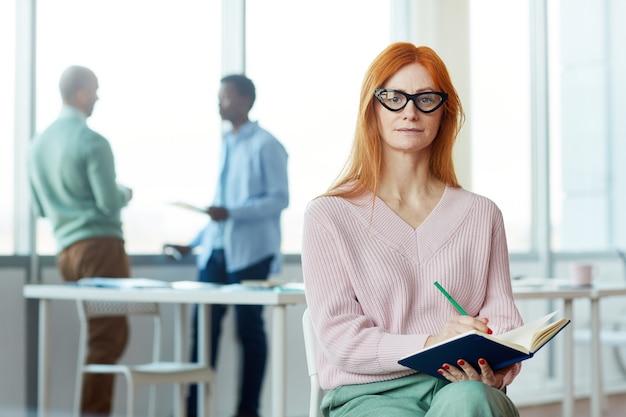 Portrait de femme d'affaires aux cheveux rouges et tenant le planificateur tout en posant dans un cadre de bureau, copiez l'espace