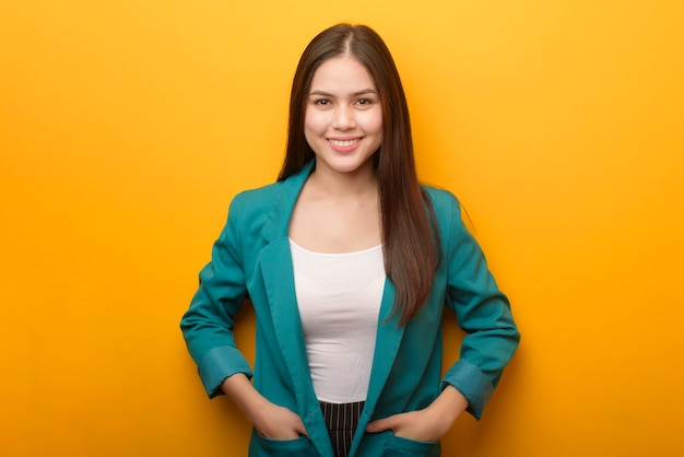 Portrait de femme d'affaires belle en costume vert sur fond jaune