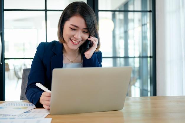 Portrait d'une femme d'affaires belle jeune entrepreneur travaillant dans un poste de travail moderne.