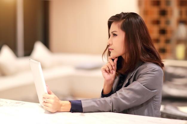 Portrait de femme d'affaires belle post à l'aide de la table et de la pensée