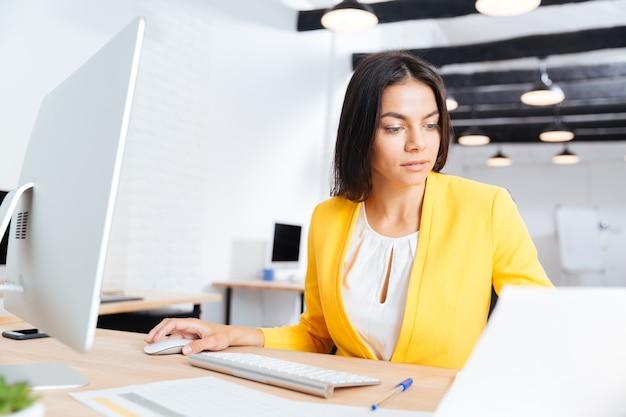 Portrait d'une femme d'affaires belle sérieuse à l'aide d'un ordinateur portable au bureau
