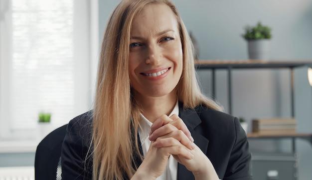 Portrait de femme d'affaires blonde souriante en costume classique assis avec les mains jointes regardant la caméra