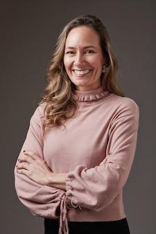Portrait de femme d'affaires blonde souriante. elle porte un chemisier bleu clair sur fond gris. a les bras croisés
