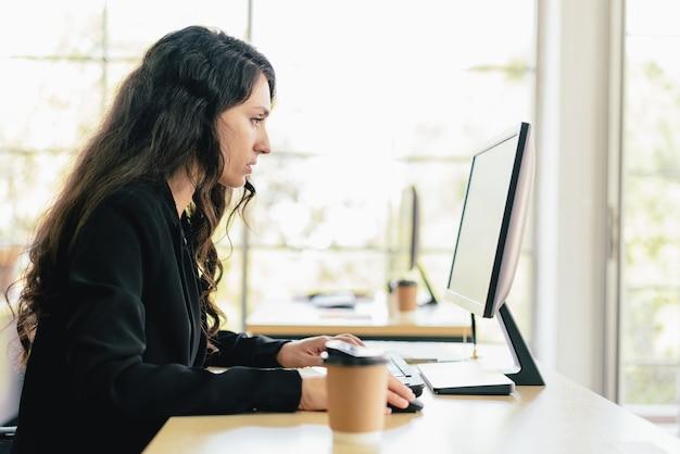 Le portrait d'une femme d'affaires caucasienne tapant au clavier et surveillant l'écran à son bureau. concerne et résout les problèmes des clients dans un siège social.