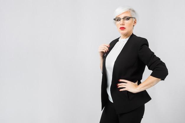 Portrait d'une femme d'affaires confiant dans un costume strict isolé sur une lumière