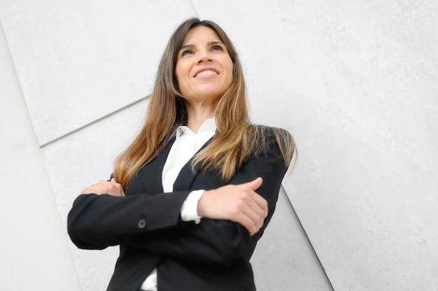 Portrait d'une femme d'affaires confiante, avec une expression heureuse debout, les bras croisés.