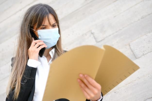Portrait d'une femme d'affaires confiante joyeuse en costume d'affaires porte un masque protecteur