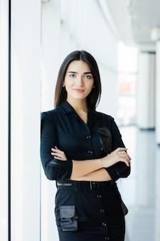 Portrait de femme d'affaires croisé mains au bureau avec fenêtres panormiques.