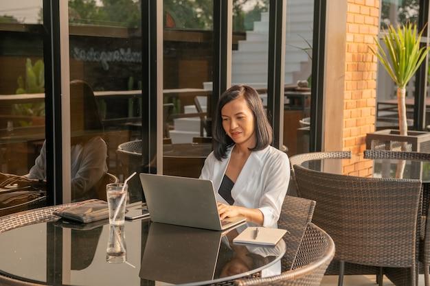 Portrait de femme d'affaires dans un café à l'aide d'un ordinateur portable