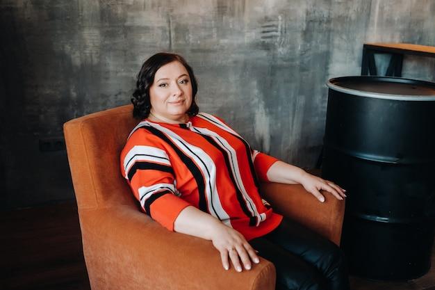 Portrait d'une femme d'affaires dans une veste rayée assise sur un canapé à l'intérieur