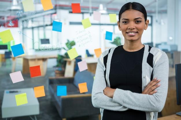 Portrait de femme d'affaires debout avec les bras croisés au bureau
