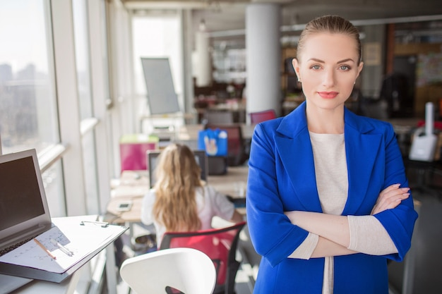 Un portrait de femme d'affaires debout près de la fenêtre avec ses mains croisées. elle regarde directement la caméra. la fille a l'air confiante et très bonne.