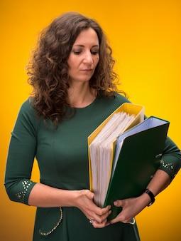 Portrait de femme d'affaires avec des dossiers sur fond jaune