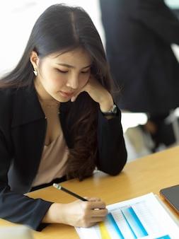 Portrait de femme d'affaires écrit sur la paperasse tout en analysant les documents commerciaux dans la salle de bureau