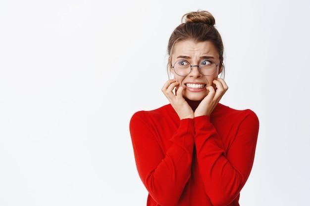 Portrait d'une femme d'affaires effrayée se rongeant les ongles et regardant à gauche effrayée, paniquée et regardant avec peur l'espace de copie, debout contre un mur blanc