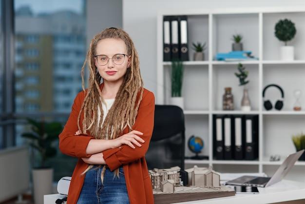 Portrait d'une femme d'affaires élégante avec des dreadlocks près de son lieu de travail avec maquette du futur bâtiment.