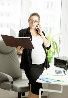 Portrait de femme d'affaires enceinte parlant par téléphone et vérifiant des documents