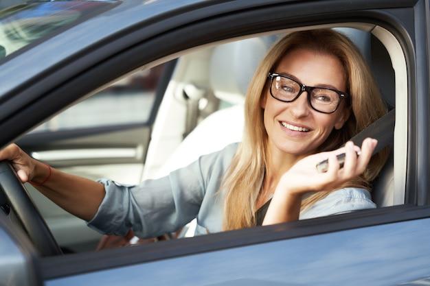Portrait d'une femme d'affaires heureuse et belle tenant des clés de voiture et souriante assise derrière
