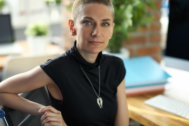 Portrait de femme d'affaires heureuse à la recherche avec calme et joie. femme d'affaires souriante se détendre sur le lieu de travail. concept d'entreprise et d'entreprise