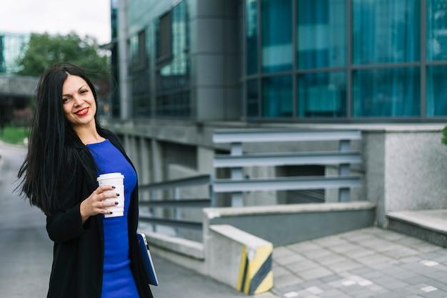 Portrait d'une femme d'affaires heureuse avec une tasse de disposition