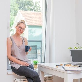 Portrait d'une femme d'affaires heureux assis avec une tasse de café