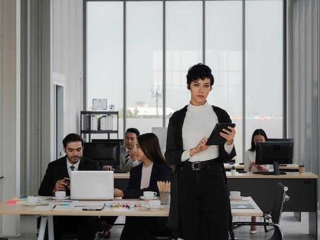 Portrait d'une femme d'affaires intelligente et attrayante tenant une tablette et impatiente de travailler avec des gens de la diversité, le leadership féminin, l'analyse commerciale et le concept de stratégie