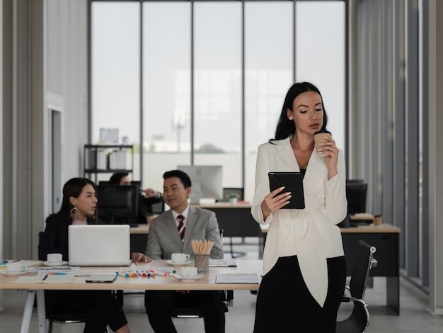 Portrait d'une femme d'affaires intelligente et séduisante regardant une tablette et buvant du café au bureau avec des personnes de la diversité travaillant, le leadership féminin, l'analyse commerciale et le concept de stratégie