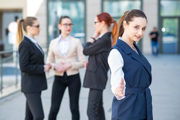 Portrait d'une femme d'affaires jeune et prospère qui tend la main